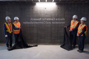 Four people with hard hats and safety vests unveiling the sign that says Alectra Centre for Research, Innovation and Commercialization