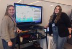 Two women stand on either side of a TV screen showing their GIS mapping project at GIS Day