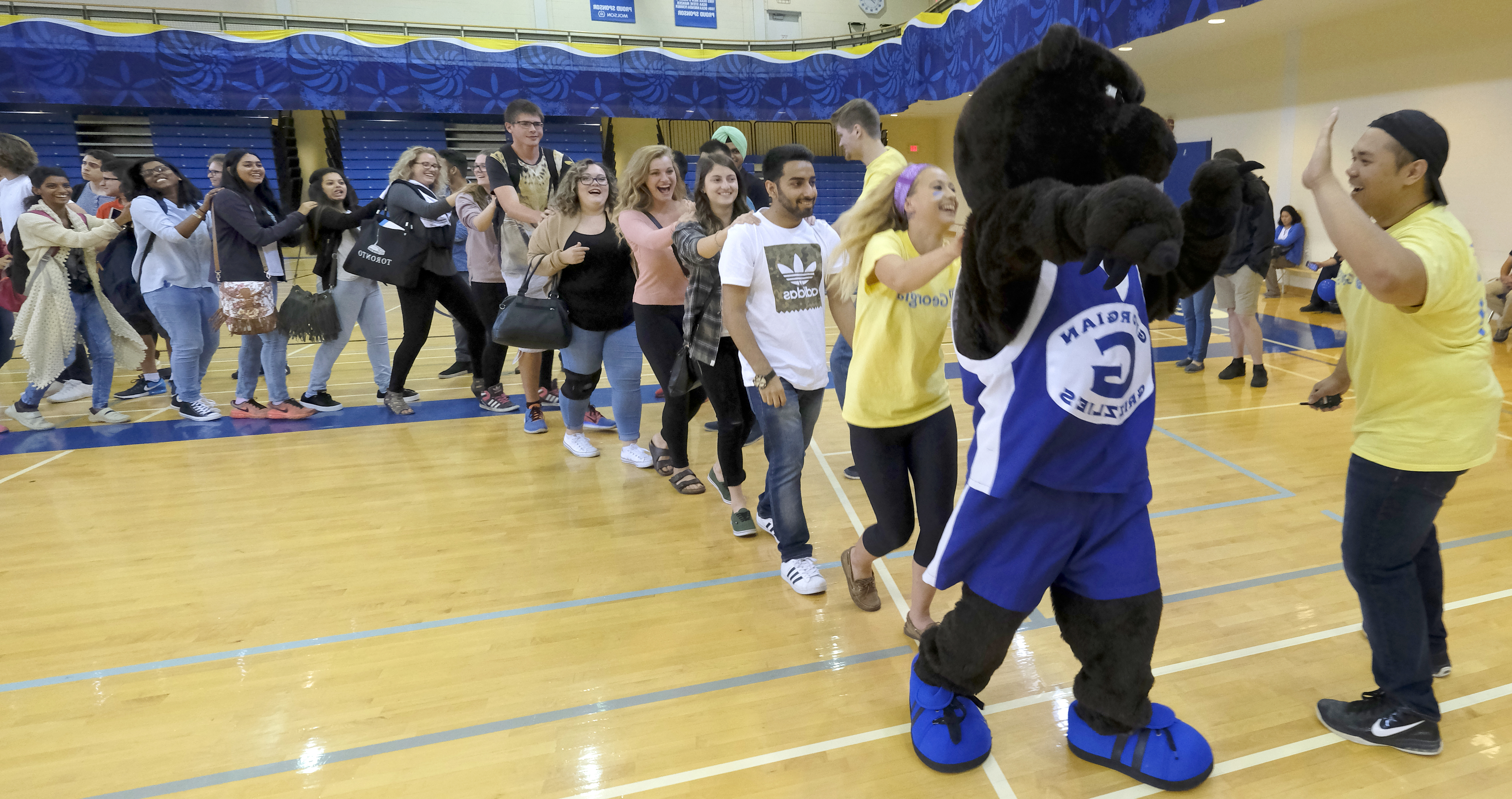 Growler the Grizzly mascot leads a conga line of students