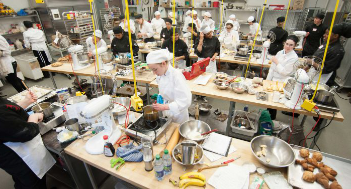 Many students in chefs uniforms are busy cooking in a baking lab.