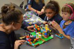 Three young girls build a house with lego while their mentor Mary Spencer helps them