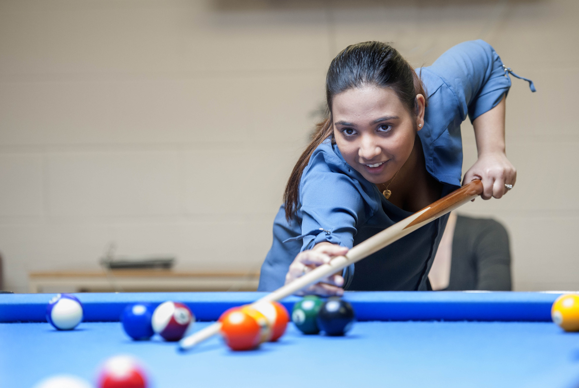 Young female student playing pool in The Den