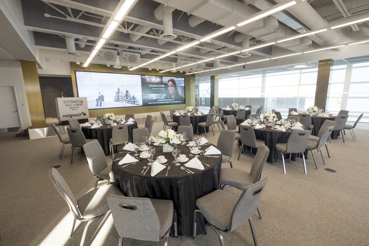 An open event space set up with dining tables and chairs, set for meal service.