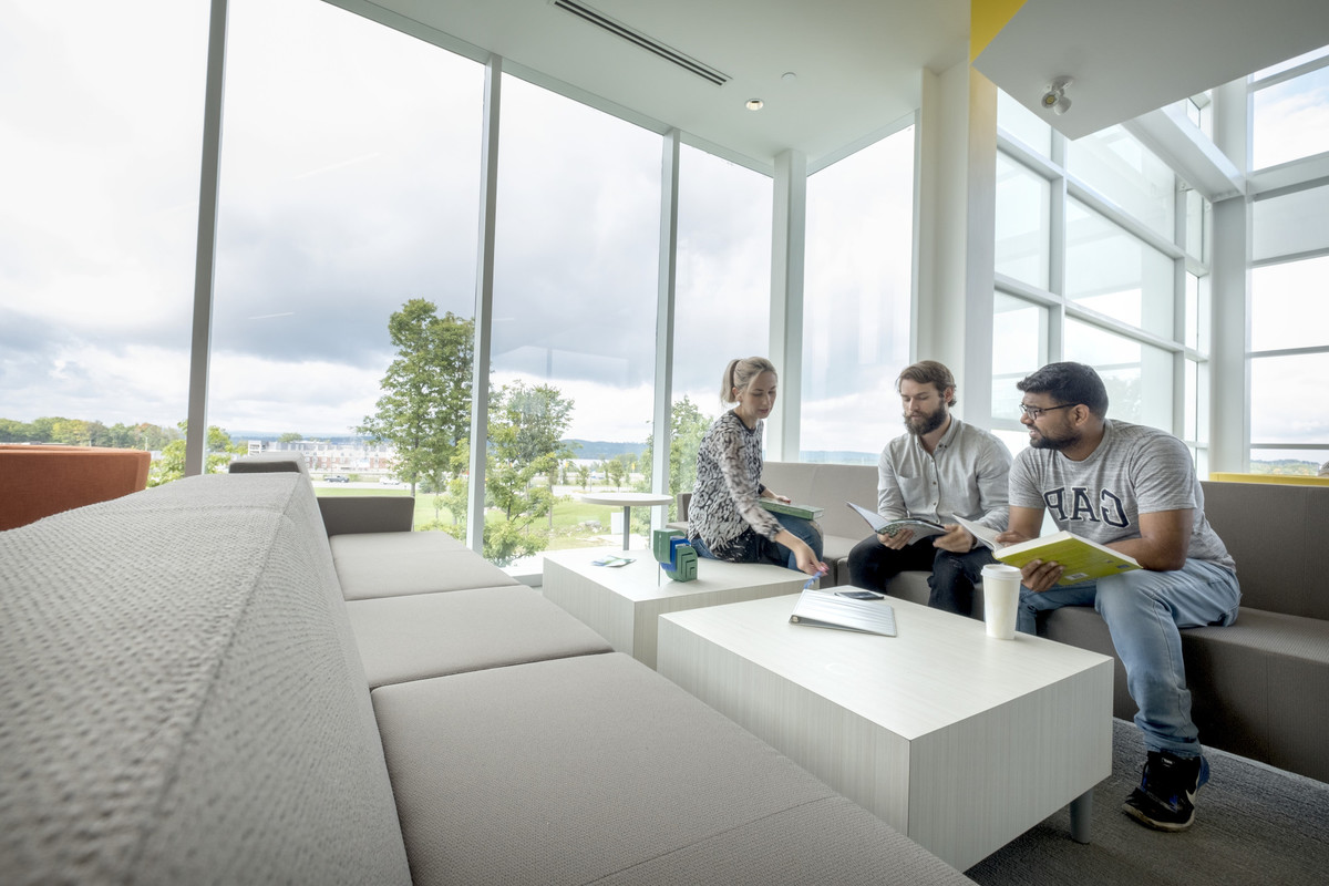 Three students sit on a couch and table in a student lounge with floor to ceiling windows.