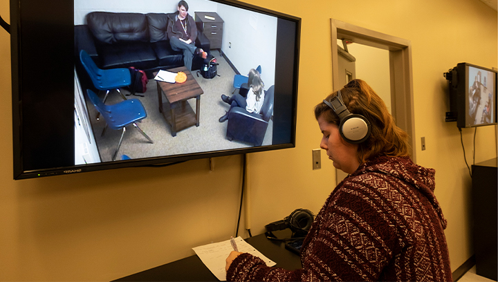 female student wearing a headset 和 taking notes while watching a counselling session through a TV screen