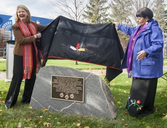Elder Lorraine McRae and President and CEO MaryLynn West-Moynes unveil the Land Acknowledgment plaque on a stone outside at the 巴里 Campus