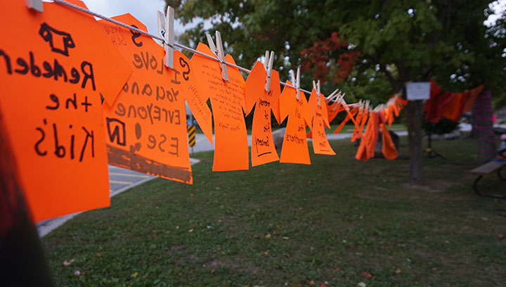 Several orange shirts hung on a clothes line between two trees