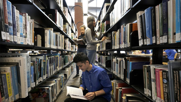 Three students standing between the book shelves 在 the library reading
