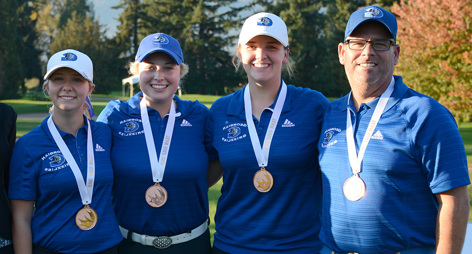 three women and one man wearing blue Georgian golf shirts and a medal around their necks standing on a golf course